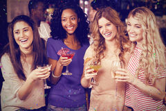 Composite image of friends drinking cocktails together while standing together Royalty Free Stock Photo