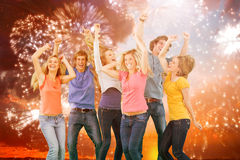 Composite image of friends partying together while laughing and smiling. Friends partying together while laughing and smiling against colourful fireworks royalty free stock photos