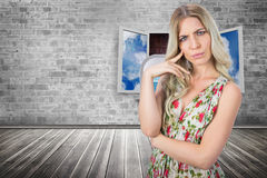 Composite image of frowning pretty blonde wearing flowered dress posing Stock Photos