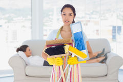 Composite image of frowning woman holding brushes and mops. Frowning women holding brushes and mops against smiling business women lying down on the couch Stock Photography