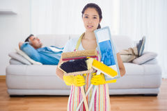 Composite image of frowning woman holding brushes and mops Royalty Free Stock Images