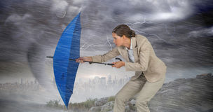 Composite image of full length of businesswoman defending with blue umbrella royalty free stock images