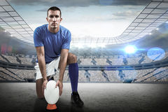Composite image of full length portrait of rugby player placing ball Royalty Free Stock Photo