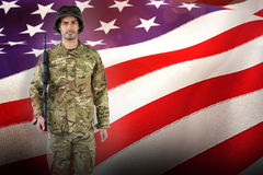 Composite image of full length portrait of soldier with rifle. Full length portrait of soldier with rifle against waving flag of america Royalty Free Stock Photos