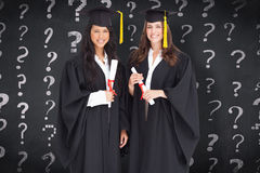 Composite image of full length shot of two women graduating Stock Images