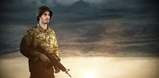 Composite image of full length of soldier holding rifle stock image