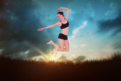 Composite image of full length of a sporty young woman jumping Royalty Free Stock Photography