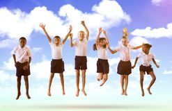 Composite image of full length of students in school uniforms jumping. Full length of students in school uniforms jumping against blue sky Royalty Free Stock Images