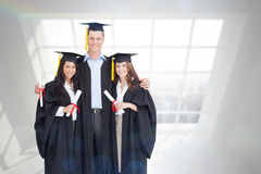 Composite image of full length of three friends graduate from college together Stock Photo