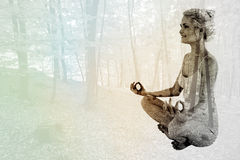 Composite image of full length of toned woman sitting in lotus position Stock Images