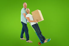 Composite image of fun older couple holding moving boxes Stock Image