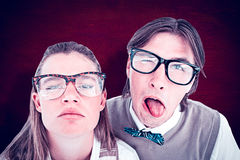 Composite image of funny geeky hipsters grimacing Stock Photography