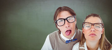 Composite image of funny geeky hipsters grimacing Royalty Free Stock Images