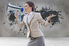 Composite image of furious stylish brown haired businesswoman shouting in a megaphone Royalty Free Stock Photos