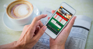 Composite image of gambling app screen. Gambling app screen against man using mobile phone by coffee and newspaper in cafe royalty free stock photo
