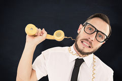 Composite image of geeky businessman being strangled by phone cord. Geeky businessman being strangled by phone cord against blackboard Royalty Free Stock Photo