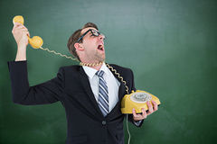 Composite image of geeky businessman being strangled by phone cord Stock Photo