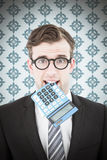 Composite image of geeky businessman biting calculator Royalty Free Stock Photos
