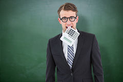 Composite image of geeky businessman biting calculator Royalty Free Stock Photography