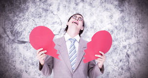 Composite image of geeky businessman crying and holding broken heart card Stock Photography