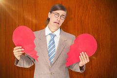 Composite image of geeky businessman crying and holding broken heart card Stock Photo