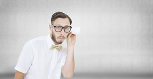Composite image of geeky businessman eavesdropping with cup Stock Images