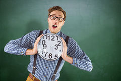 Composite image of geeky businessman holding a clock Stock Images