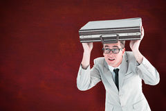 Composite image of geeky businessman holding his briefcase over head Stock Photos