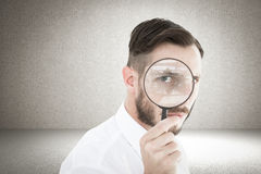 Composite image of geeky businessman looking through magnifying glass Stock Photos