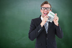 Composite image of geeky businessman pointing to calculator Stock Image