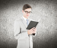 Composite image of geeky businessman reading black book Royalty Free Stock Photography