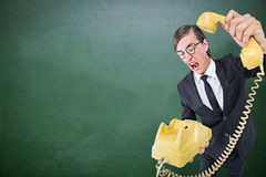 Composite image of geeky businessman shouting and hanging up the telephone. Geeky businessman shouting and hanging up the telephone against green chalkboard Royalty Free Stock Photography