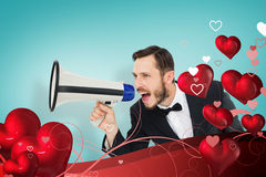Composite image of geeky businessman shouting through megaphone. Geeky businessman shouting through megaphone against blue vignette background Stock Images