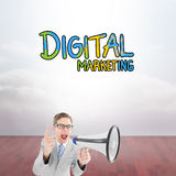 Composite image of geeky businessman shouting through megaphone. Geeky businessman shouting through megaphone against clouds in a room Royalty Free Stock Image