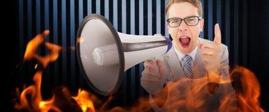Composite image of geeky businessman shouting through megaphone. Geeky businessman shouting through megaphone against dark grey room Royalty Free Stock Image