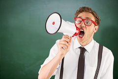 Composite image of geeky businessman shouting through megaphone. Geeky businessman shouting through megaphone against green chalkboard Stock Photography
