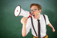 Composite image of geeky businessman shouting through megaphone. Geeky businessman shouting through megaphone against green chalkboard Royalty Free Stock Images