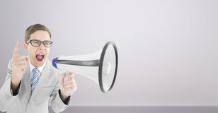 Composite image of geeky businessman shouting through megaphone Royalty Free Stock Photo