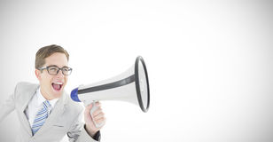 Composite image of geeky businessman shouting through megaphone. Geeky businessman shouting through megaphone against white background with vignette Royalty Free Stock Images