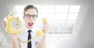 Composite image of geeky businessman shouting at retro phone. Geeky businessman shouting at retro phone against room with large window showing city Royalty Free Stock Image