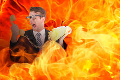 Composite image of geeky businessman shouting at telephone. Geeky businessman shouting at telephone against fire Royalty Free Stock Images