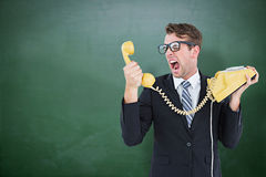 Composite image of geeky businessman shouting at telephone. Geeky businessman shouting at telephone against green chalkboard Stock Photography
