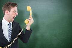 Composite image of geeky businessman shouting at telephone. Geeky businessman shouting at telephone against green chalkboard Stock Image