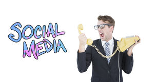 Composite image of geeky businessman shouting at telephone. Geeky businessman shouting at telephone against social media Stock Photos