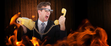 Composite image of geeky businessman shouting at telephone. Geeky businessman shouting at telephone against wooden table Royalty Free Stock Images