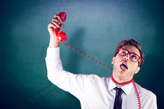 Composite image of geeky businessman strangling himself with telephone Stock Photo