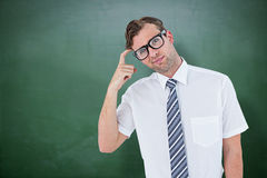 Composite image of geeky businessman thinking with finger on temple Stock Photography