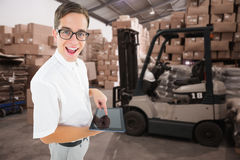 Composite image of geeky businessman using his tablet pc. Geeky businessman using his tablet pc against warehouse worker loading up pallet Royalty Free Stock Photos