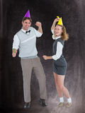 A Composite image of geeky couple dancing with party hat Royalty Free Stock Image
