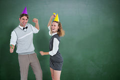 Composite image of geeky couple dancing with party hat Royalty Free Stock Photography